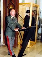 Uniformierter Mann steht am Rednerpult neben einer Vitrine.