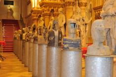 Steinbüsten und Skulpturen hintereinander aufgestellt.