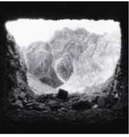 Unscharfes Schwarz-Weiß-Foto eines Berggipfels, aus einer Höhle heraus betrachtet.