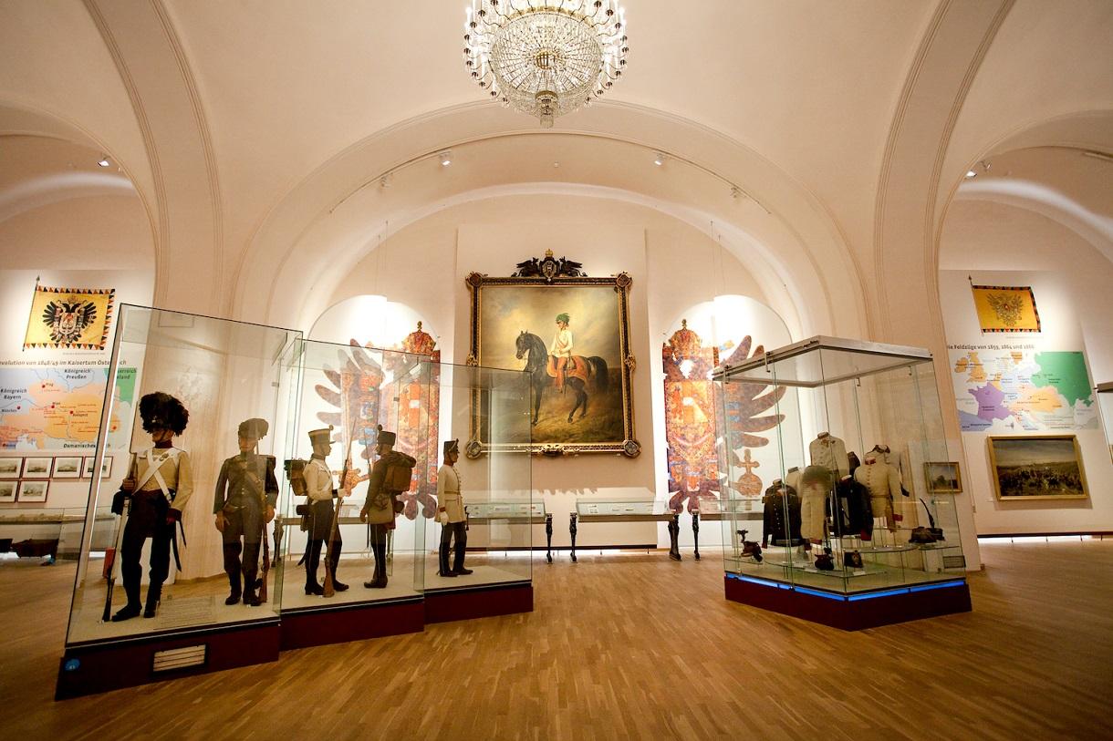 Vitrinen mit Schaufensterpuppen in Uniform, Gemälde, Wappen und Landkarten an den Wänden.