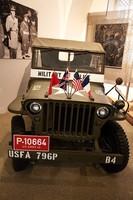 Militärjeep mit den Fahnen von Sowjetunion, Großbritannien, USA und Frankreich auf der Motorhaube.