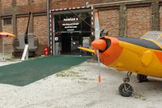 Eingang zum Hangar, schräg daneben eine bunte Propellermaschine.