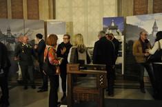 Viele Besucher im Gespräch vor großen Bildern auf Staffeleien.