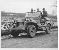 Schwarz-Weiß-Foto von drei Soldaten in einem Jeep.