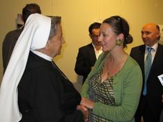 Nonne im Gespräch mit einer Frau.
