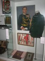 Orden, Medaillen, eine Uniformjacke und ein Porträt von einem General in einer Vitrine.