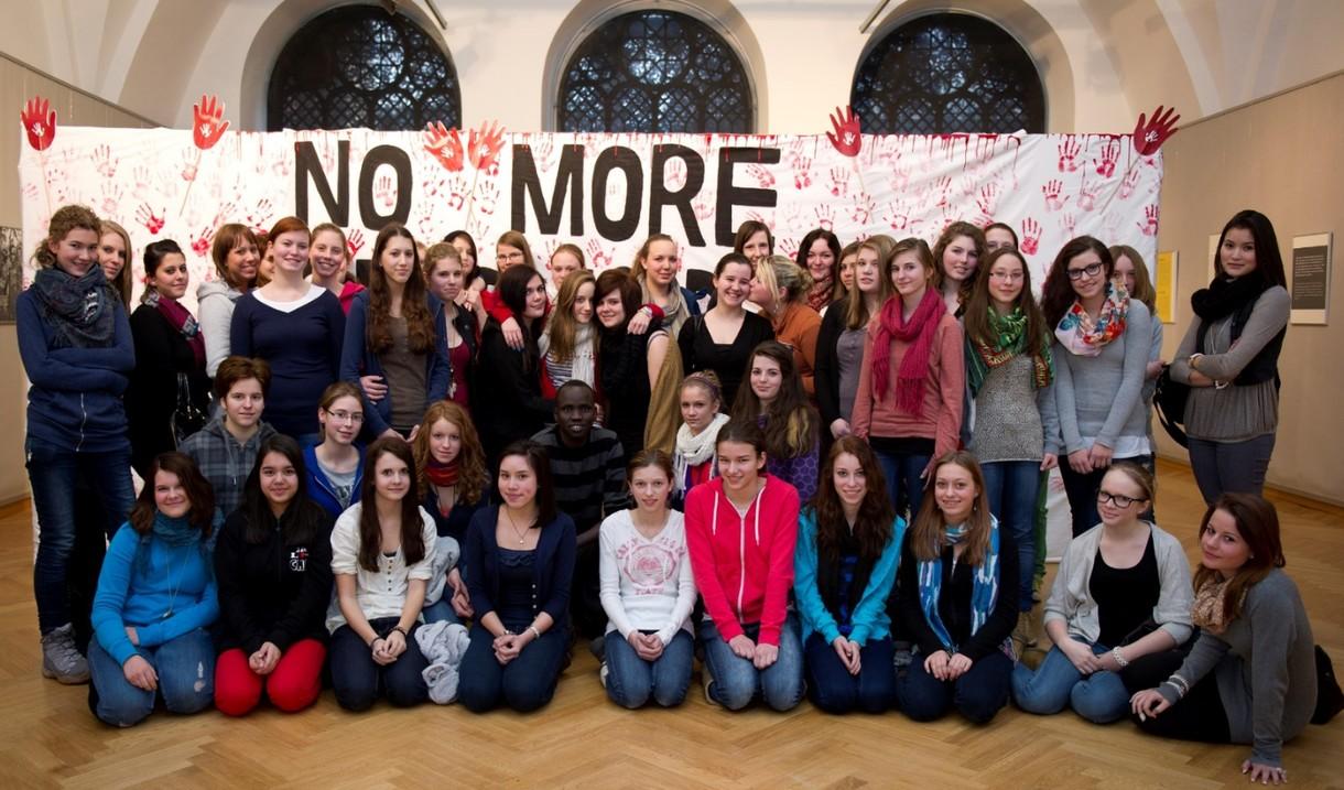 """Gruppe von Schülerinnen und Schülern vor einem Transparent, auf dem """"No more"""" steht."""