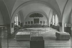 Schwarz-Weiß-Foto mit Schaukästen und Vitrinen im Ausstellungsraum.