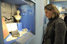 Besucherin betrachtet eine Vitrine mit Dokumenten.