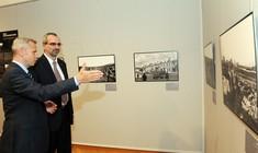 Kurator zeigt einem Mann im Anzug ein Foto an der Wand.
