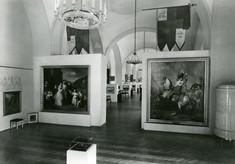 Schwarz-Weiß-Foto zeigt Schauwände mit Gemälden, darüber Flaggen und ein Kronleuchter.