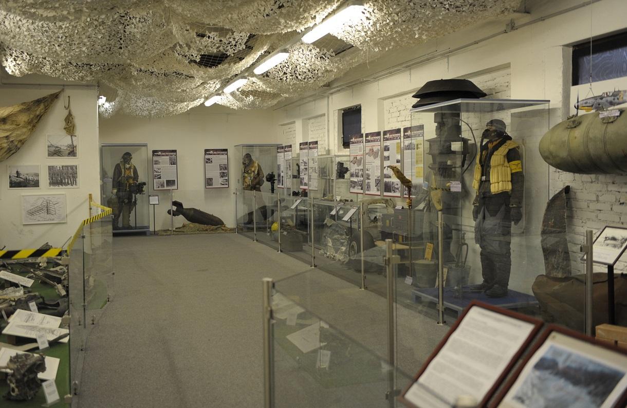 Niedriger Raum mit Bomben, Fliegeruniformen und Infotafeln an den Wänden.