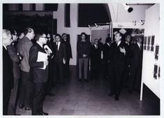 Besucher in dunklen Anzügen betrachten die Ausstellung.