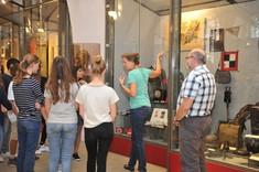 Eine Frau steht vor einer Vitrine und zeigt auf ein Ausstellungsstück, um sie herum stehen Jugendliche, hinter ihr steht ein älterer Herr.