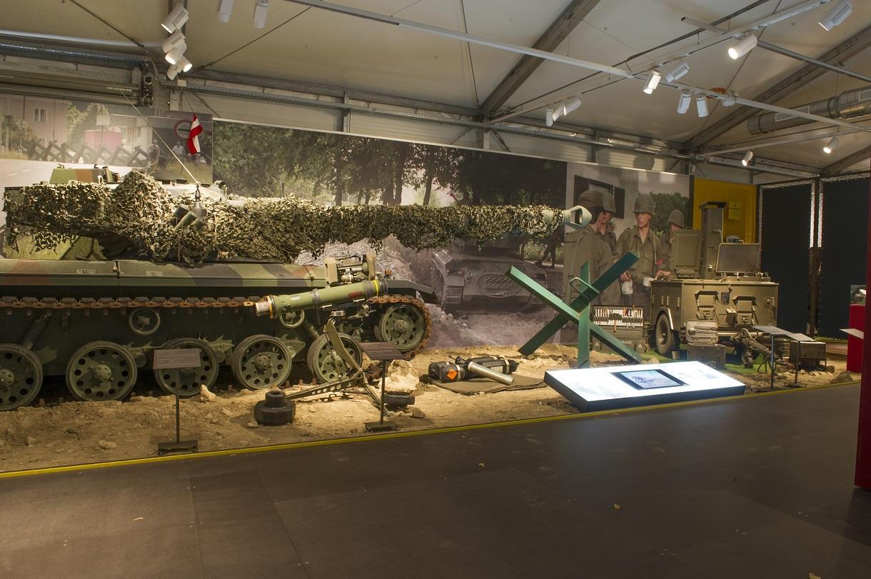 Panzer mit getarntem Zielrohr hinter Absperrkette im Ausstellungsraum.
