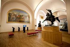 Gemälde mit Multimedia-Station und Sitzbänken davor, auf einem Holzpodest im Raum eine kleine Reiter-Statue