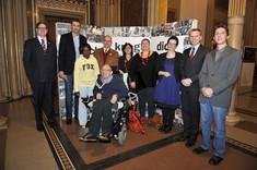 Mehrere Menschen stehen zusammen und schauen in die Kamera, Männer und Frauen, vor ihnen ein Mann im Rollstuhl.
