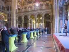 Frau am Rednerpult auf einer Bühne, vor ihr an Stehtischen zahlreiche Besucher.