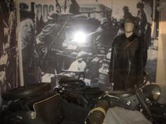 Schaufensterpuppe in Uniform mit Helm neben Motorrad stehend.