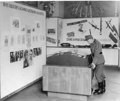 Schwarz-weiß-Foto eines Soldaten in einen Schaukasten blickend.