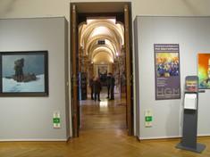 Aufnahme einer Gruppe von Besuchern durch die Museumsfluchten, links und rechts hängen Gemälde.