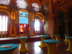 Leere Bühne und Stehtische verteilt im Saal.