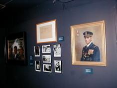 Mehrere gerahmte Fotografien und Gemälde an der Wand.