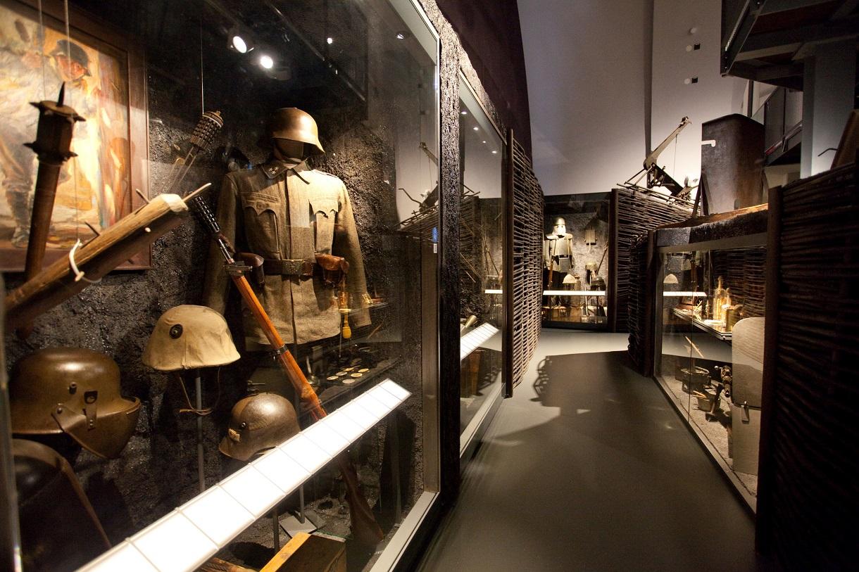 Uniform, Helme und Waffen in einer Vitrine.