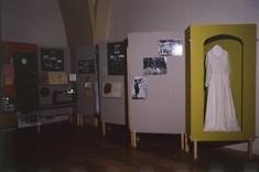 Hintereinander aufgestellte Schauwände mit aufgeklebten Fotografien und davor in einem Schrank ein Damenkleid.