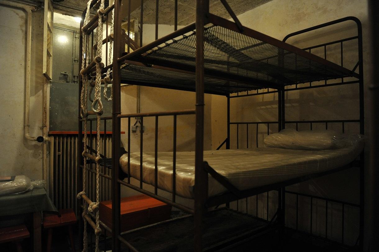 Doppelbett aus Metall, am Fußende eine Strickleiter.
