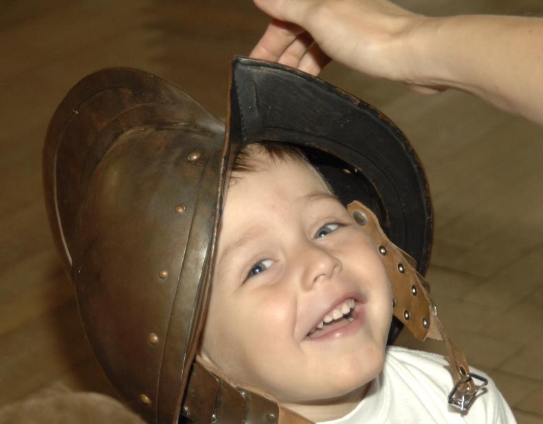 Ein lachendes Kind mit einem Ritterhelm.