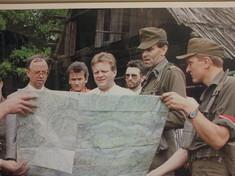 Gerahmte Fotografie mit Soldaten, die vor einer Holzhütte eine Landkarte halten.