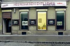 """Geschäftslokal in Wien mit drei beleuchteten Schaufenstern und darüber der Schriftzug """"Heeresgeschichtliches Museum""""."""