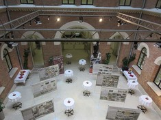 Blick von oben auf Ausstellungsraum mit schräg aufgestellten Schauwänden und Stehtischen dazwischen.