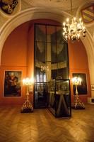Ausstellungsraum mit einer hohen Vitrine mit Teppichen.