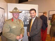 Mann in Uniform und Mann in Anzug stehen vor einer Fotografie zusammen und lächeln in die Kamera.