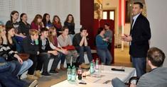Damir Hamidovic steht vor einer Gruppe Jugendlicher, die vor ihm sitzen.