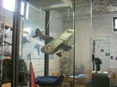 Modell eines Militärflugzeugs in einer Vitrine hängend.