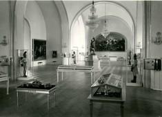 Schwarz-weiß-Foto mit Schaukästen und Vitrinen im Raum verteilt, an der Decke ein Kronleuchter.
