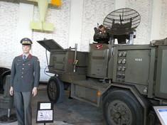 Schaufensterpuppe in Uniform neben einem Militärkraftwagen.