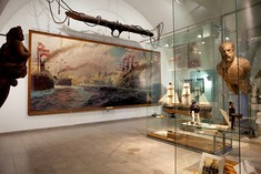 Gallionsfiguren links und rechts, in der Mitte ein großes Gemälde mit Kriegsschiffen, daneben ein Segelschiffmodell.