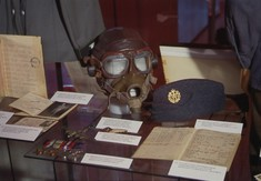 Briefe, Dokumente und eine Fliegermaske in einem Schaukasten.