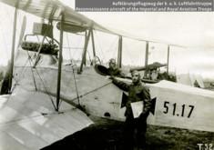 Ein PIlot sitzt, ein PIlot steht neben einem Doppeldeckerflugzeug.