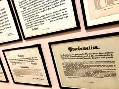 Gerahmte Dokumente und amtliche Proklamationen an der Wand.