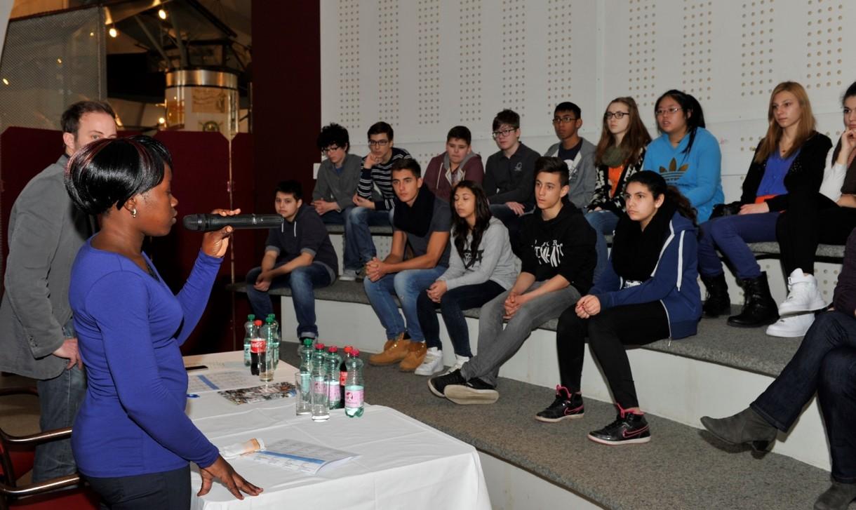 Christine Akello spricht vor einer Gruppe Jugendlicher, die vor ihr sitzt.
