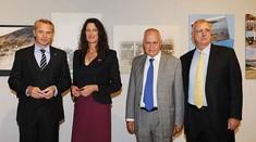 Drei Männer im Anzug und eine Frau stehen nebeneinander und schauen in die Kamera.