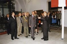 Mehrere Männer in Anzügen und einer in Uniform. Vor ihnen steht der Kurator und zeigt etwas in der Ausstellung.