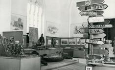 Schwarz-weiß-Foto mit verschiedenen militärischen Wegweisern und Bildern auf Schauwänden.