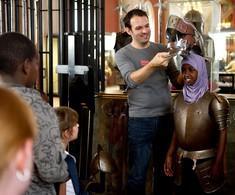 Kulturvermittler setzt einem Kind in Ritterrüstung einen Helm auf.