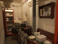 Küche mit Herd und einem Regal, auf einem Tisch steht Geschirr gestapelt.